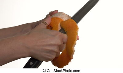 Girl cuts a knife peel grapefruit. White background....