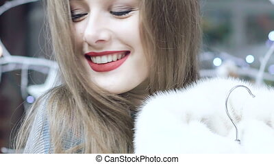 Beautiful girl chooses a fur coat in the shop Slowly.