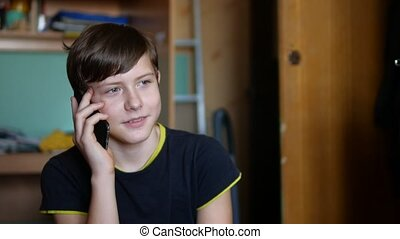 Teen boy talking on the phone smartphone indoor - Teen boy...