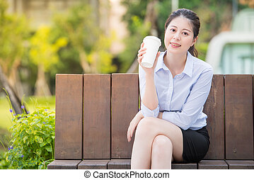 beautiful asian business woman drinking coffee on park...