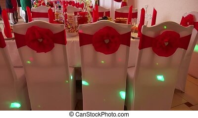 chairs in a restaurant decorated with ribbons flashes...