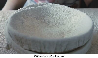 Woman's hands sieving flour. Slowly - Woman's hands sieving...
