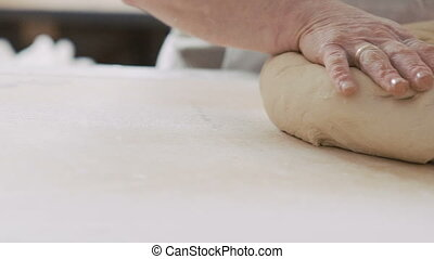 Women kneading dough for bread on table. Slowly.