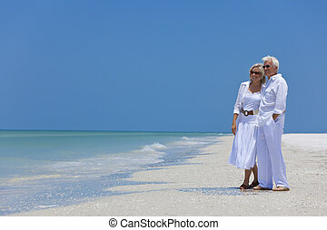 Happy Senior Couple Looking To Sea on A Tropical Beach -...