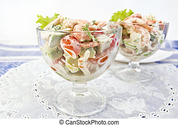 Salad with shrimp and avocado in glass on white napkin
