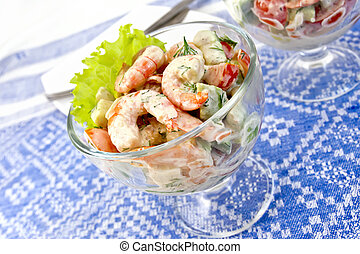 Salad with shrimp and avocado in glass on tablecloth