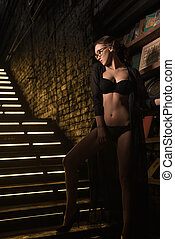 Seductive beauty in black lingerie on stairs