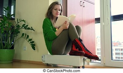 Frozen Woman Reading Book Sitting On Radiator And Adjusting...