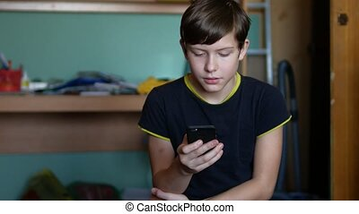 Teenage boy holding a smartphone online games web search social media