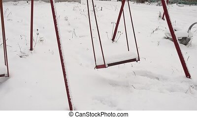 old swing at the playground in snow the winter - old swing...