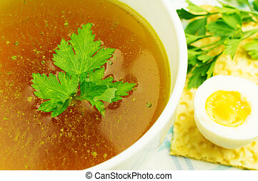 Bouillon, broth, clear soup in a white cup with a loaf,...