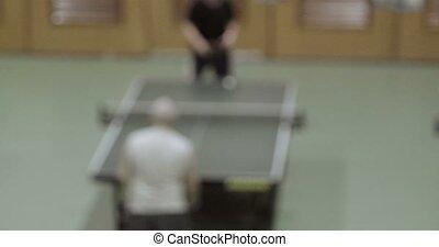 Two senior people play ping-pong tennis defocused footage,...