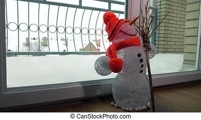 Funny toy handmade snowman against snowstorm behind the...