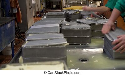 Metal boxes with butter at dairy plant shot - View of metal...