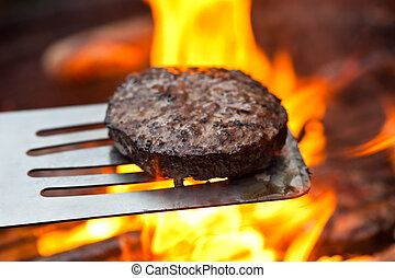 Grilled burger - Flame grilled beefburger on a BBQ