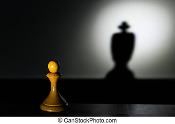 a chess pawn casting a king piece shadow in dark concept of...