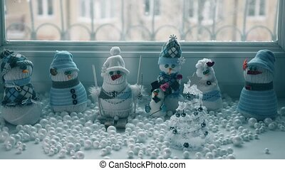 Several toy handmade snowmen and snowstorm outside the...