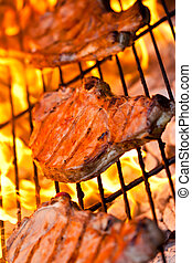 Three pork chops on the BBQ - Three flamed grilled pork...