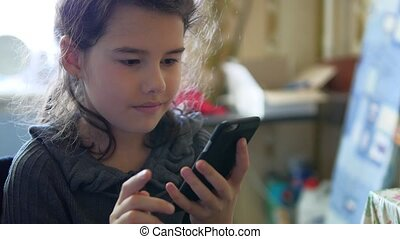 Girl breakfast in the kitchen playing smartphone online...