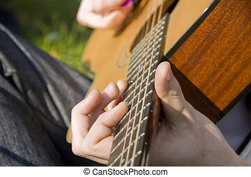 close up of a men playing on his guitar