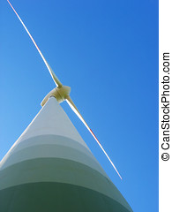Wind power - Worms eye view of wind turbine against blue sky...