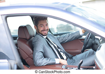 Portrait of an handsome smiling business man driving his car...