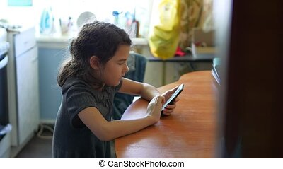 Girl breakfast in the kitchen social media playing smartphone online games sits by the table
