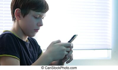 Teenage boy holding a smartphone online games web search...