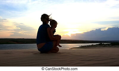 Silhouette Mother Sits Carries Small Girl by Lake at Dusk -...