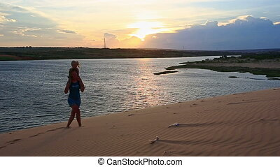 Silhouette Mother Carries Small Girl on Dunes at Dusk by Lake