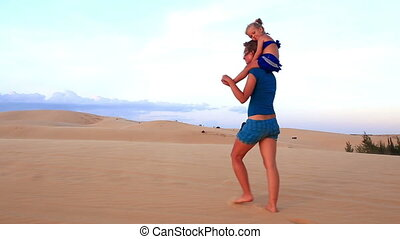 Mother Carries Small Girl on Shoulders on Dunes against Sky...