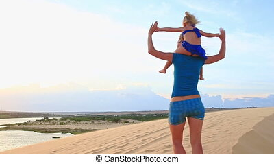 Mother Carries Small Girl on Shoulders Turn around on Dune...
