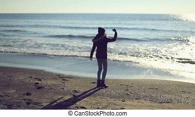 Teen girl taking photo on the beach. Handheld shot