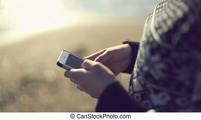 Teen girl using smartphone on the beach. Handheld shot