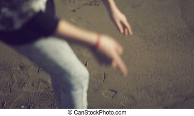 Teen girl drawing heart shape on the sand. Handheld shot