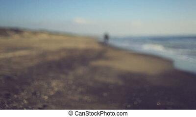 Teen girl running on the beach. Handheld shot