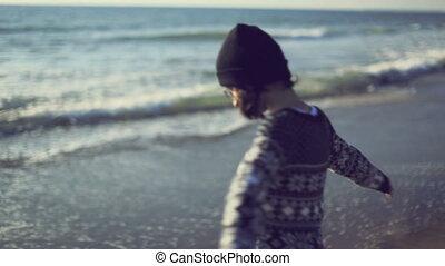 Teen girl enjoying nature on the beach. Handheld shot