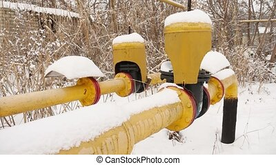 yellow gas pipe in the snow winter heating gas - yellow gas...