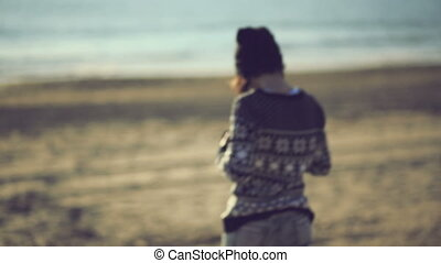 Teen girl taking photo on the beach with an old film camera....