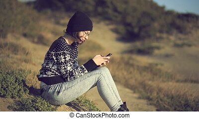 Teen girl using smartphone on the beach and smiling at...