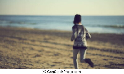 Teen girl running on the beach. Handheld shot