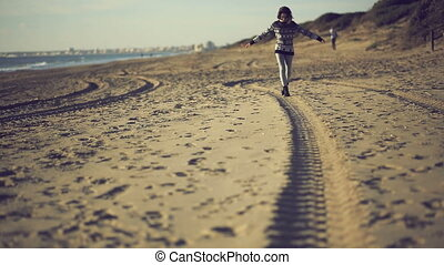 Teen girl walking on the beach. Handheld shot