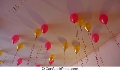 red yellow balloons hanging on the ceiling of the holiday -...