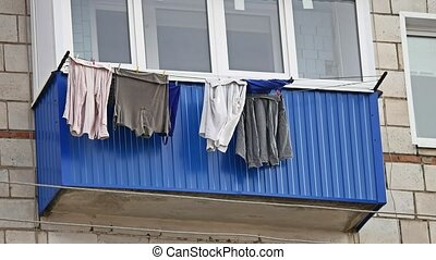 Drying clothes hanging on a balcony of the house - Drying...