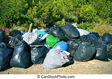 garbage bags - a pile of full garbage bags in a dump