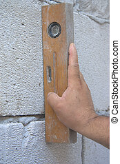old bubble level on white brick wall - worker hand measuring...