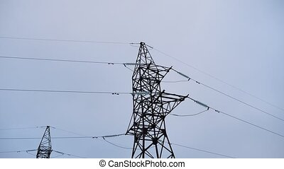Electrical tower with cables against the gray electricity...