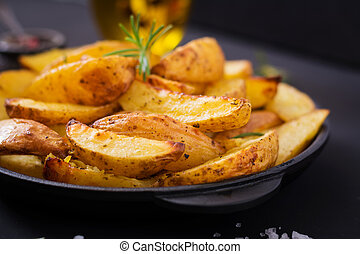 Ruddy Baked potato wedges with rosemary and garlic on a dark...
