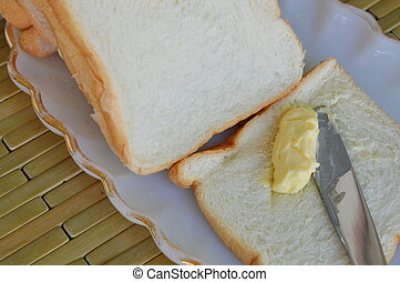 butter with table knife on bread