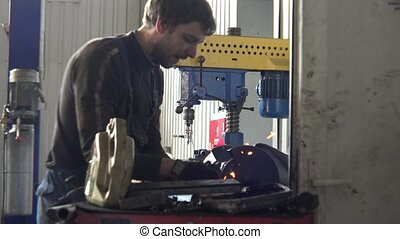 Mechanic polishing car part on polishing machine in a...